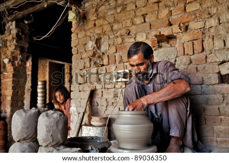 Indian muslim potter making a terracotta vase - stock photo