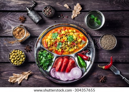 Indian Mutter paneer dish with spices on the wooden background