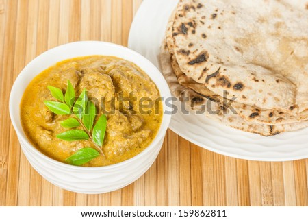 Indian Mutton Curry and Chapati - Closeup view of delicious mutton curry served with fluffy chapati (Indian bread). Curry prepared using onions, curry leaves, garlic, ginger, cayenne & black pepper. - stock photo