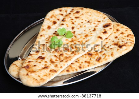 Indian naan bread on stainless steel platter.