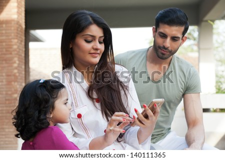 indian or multi ethnic family , mother showing something to her daughter on Phone tablet
