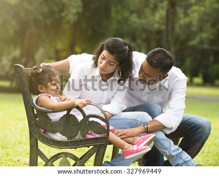 indian parent dealing with daughter with tantrum - stock photo