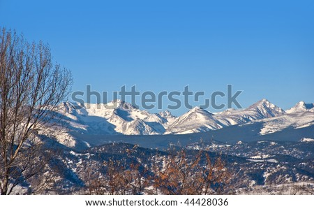Indian Peaks area on the Rocky Mountain Continental Divide in Colorado as seen from open space east of Boulder capped with snow in winter - stock photo