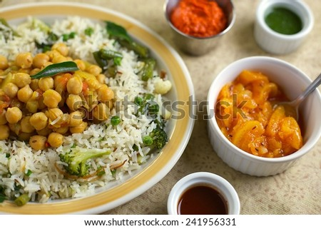 Indian Rice Pulao with Chick Peas, Broccoli, Peas and Sauces - stock photo