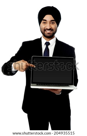 Indian salesman presenting brand new laptop - stock photo