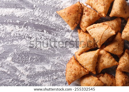 Indian samosa pastry on a floured table. horizontal view from above  - stock photo