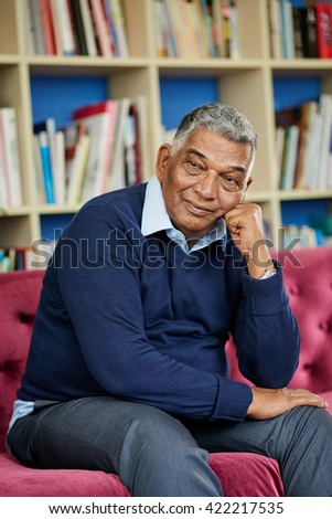 Indian senior man contemplating when resting on sofa - stock photo
