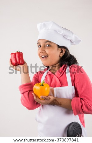 indian small girl chef with capsicum, isolated on white background, indian little chef, asian girl chef - stock photo