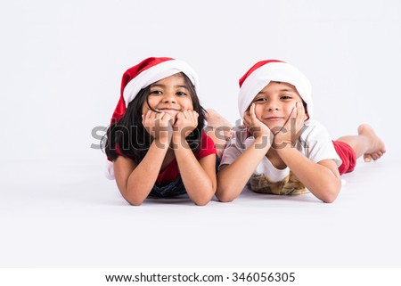 indian small kids showing happiness of christmas, christmas and happy kids, isolated on white background, indian kids and christmas, asian kids and christmas, both hands on chin, indian baby girl - stock photo