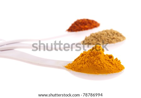 indian spices in measuring spoons (curcuma, coriander, red pepper flakes) isolated on white background (shallow DOF, focus on first) - stock photo