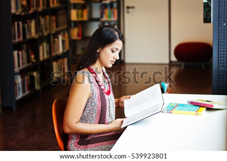 Indian student reads a book at the library, indoor