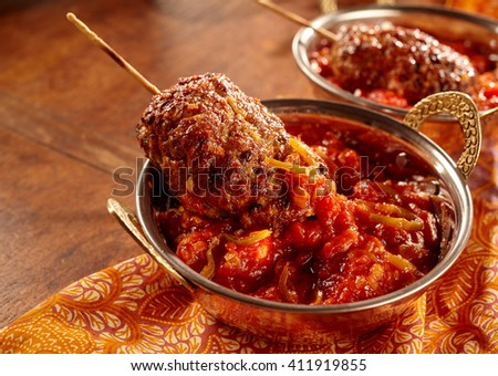 Indian style cuisine of minced meat rolls with skewers dipped in hot sauce over decorative table cloth - stock photo