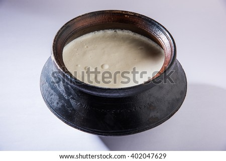 Indian sweet Lassi made up of milk, curd, sugar and salt mixed with ice cubes, prepared in traditional earthen pot , India's favourite summer time cold drink