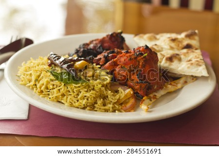 Indian tandoori chicken with fresh naan and tamarind rice - stock photo