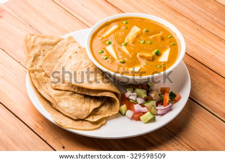 indian tasty food paneer butter masala served with roti / chapati / fulka / indian bread and green salad