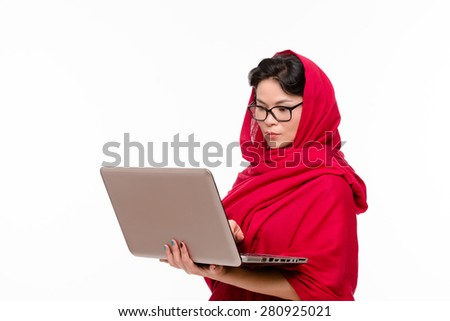 Indian teacher dressed in traditional red-coloured sari and with glasses on is so serious looking into her computer and trying to find the necessary information. - stock photo
