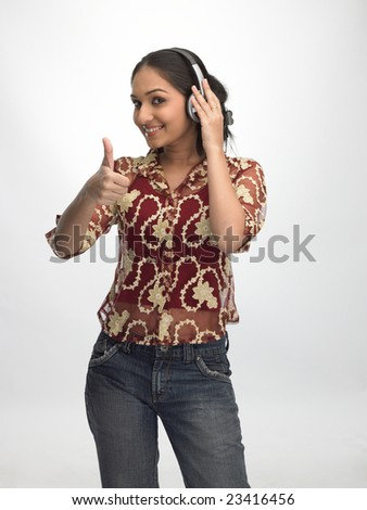 Indian teenage girl saying excellent listening to music - stock photo