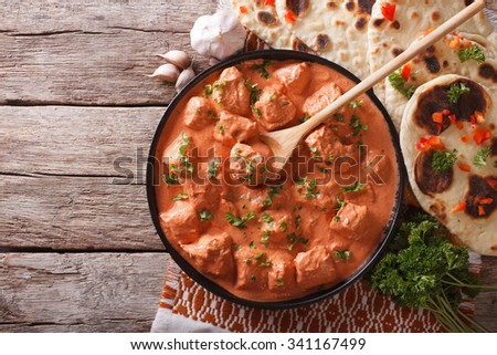 Indian tikka masala chicken and naan flat bread on the table. horizontal top view