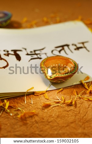 Indian traditional lamps on a religious book - stock photo