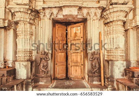 Indian traditional style design at entrance of historical Hindu temple with collumns, wooden door and sculptures, India