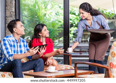 Indian waitress taking orders of two customers in cafe or restaurant - stock photo