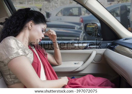Indian woman depressed and sitting in car with hand on her head while wearing traditional clothes