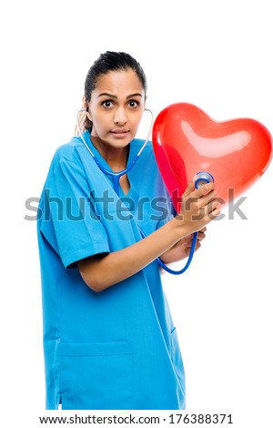 Indian woman doctore listening to heartbeat smiling confident stethoscope white background - stock photo