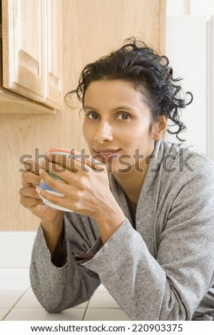 Indian woman drinking coffee in kitchen - stock photo