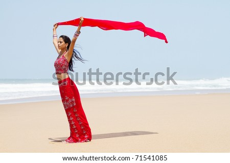 indian woman holding sari on windy beach - stock photo