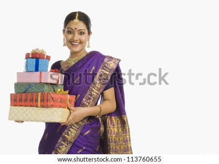 Indian woman in traditional Assamese dress holding gifts and smiling - stock photo