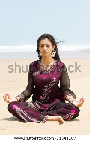 indian woman in traditional clothing on beach meditation - stock photo