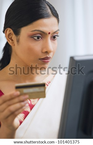 Indian woman in traditional clothing online shopping - stock photo