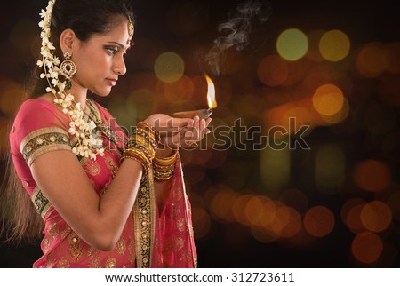 Indian woman in traditional sari lighting oil lamp and celebrating Diwali or deepavali, fesitval of lights at temple. Female hands holding oil lamp, beautiful lights bokeh background. - stock photo