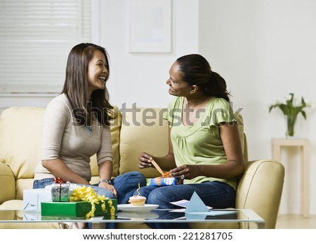 Indian woman opening gift from friend - stock photo
