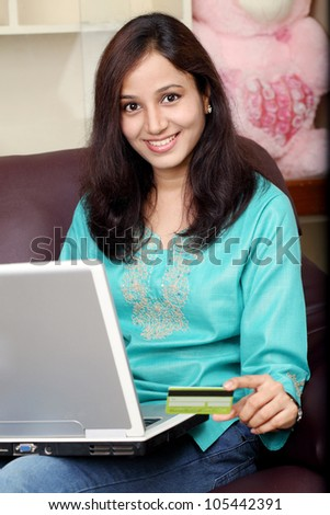 Indian woman shopping on line from home - stock photo