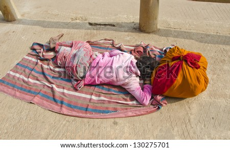 indian woman with colorful sari sleeping on pavement in Varanasi near Ganges, India - stock photo