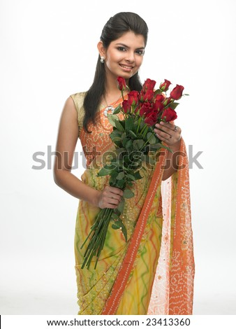 Indian woman with sari carrying bunch of red roses - stock photo