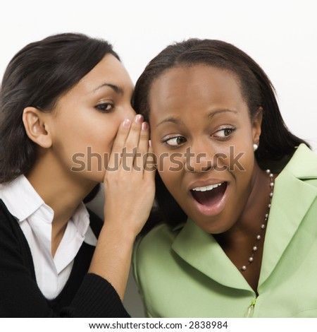 Indian young adult woman whispering in ear of mid-adult African-American woman. - stock photo