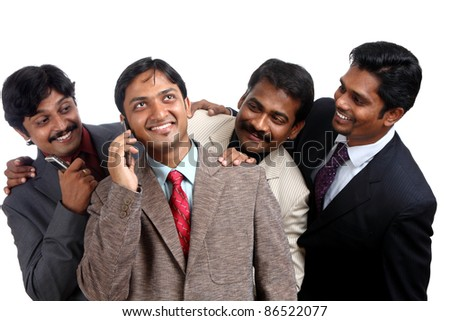 Indian young businessman talking in mobile others listening him. - stock photo