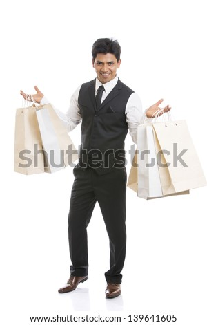 Indian young businessman with shopping bags on white background. - stock photo