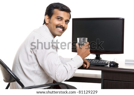Indian young happy businessman with water in office