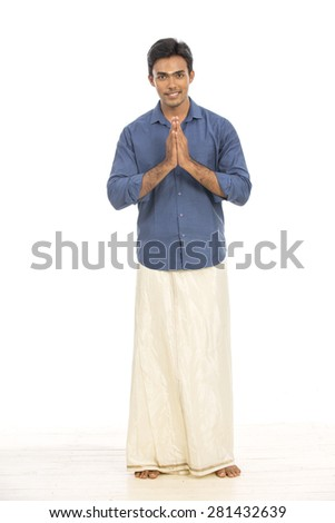 Indian young man greeting in traditional dress on white background. - stock photo