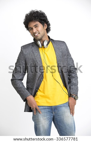 Indian young man in urban style with headphone on white. - stock photo