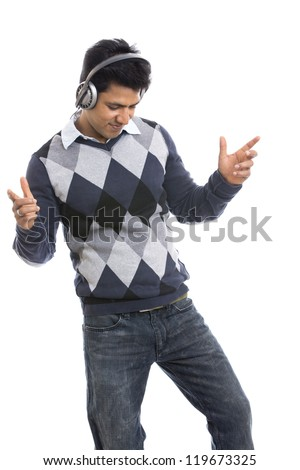 Indian young man listing music in headphone on white. - stock photo