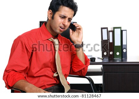 Indian young man talking in mobile phone at office - stock photo