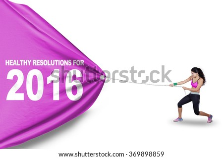 Indian young woman wearing sportswear and pulling a flag with text of healthy resolution for 2016 - stock photo