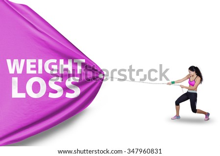 Indian young woman wearing sportswear and pulls a flag with weight loss text, isolated on white background - stock photo