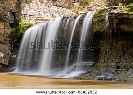 Indiana's Upper Cataract Falls (left side only). The falls has a hollowed out cavity behind it. - stock photo
