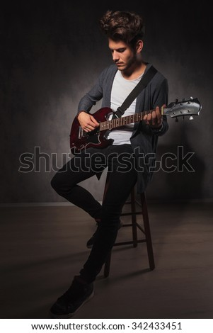 indie artist playing guitar sitting on a chair in studio background while looking down