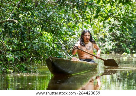INDIGENOUS ADULT MAN ON TYPICAL WOODEN CANOE CHOPPED FROM A SINGLE TREE NAVIGATING MURKY WATERS OF ECUADORIAN AMAZONIAN PRIMARY JUNGLE  - stock photo